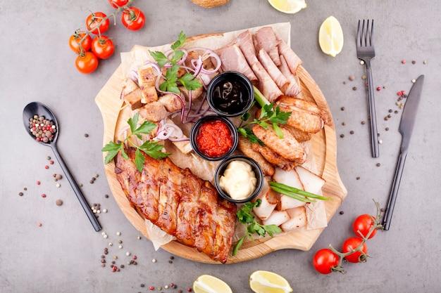 Der fleischteller ist mit schnitten und steaks gefüllt, die mit kräutern, kirschtomaten und zitronen dekoriert sind. das konzept der fleisch- oder bier vorspeise.