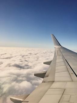 Der flügel des flugzeugs in einer höhe während des fluges der wolken im hintergrundbild