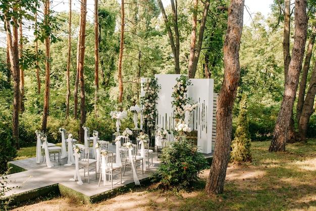 Der flur der hochzeitszeremonie mit einem bogen aus weißer textilsoda und blumen hofhochzeit