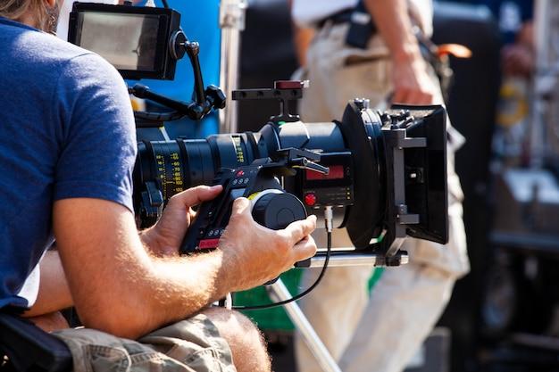 Der focus puller hält das drahtlose follow-focus-system während des filmvorgangs fest