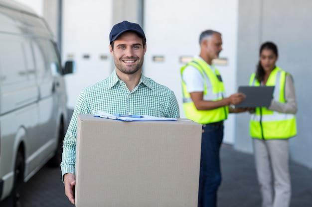 Der fokus des lieferers hält einen karton und lächelt in die kamera