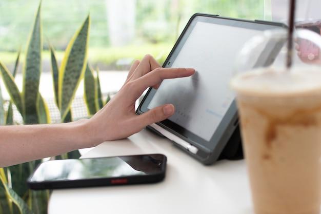 Der fokus seiner hand lag auf dem tablet-bildschirm, der auf dem tisch lag, auf dem ein handy und ein glas wasser standen.