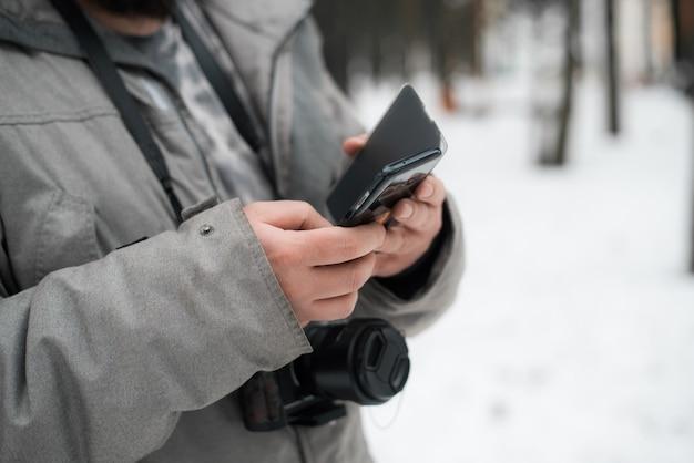 Der fotograf benutzt im winter draußen ein mobiltelefon. mann in einer jacke und mit einer kamera, nahaufnahme. selektiver fokus