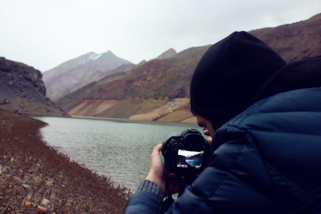 Der fotograf fotografiert den sonnenuntergang in den bergen