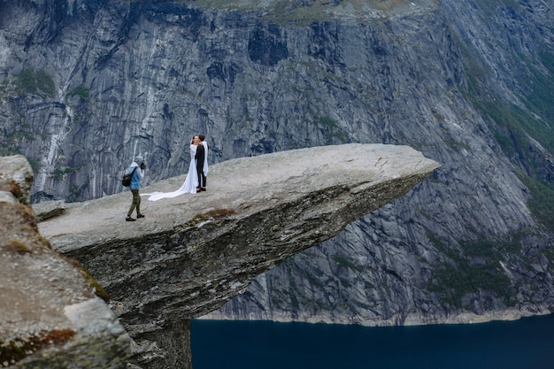 Der fotograf fotografiert ein frisch verheiratetes paar auf einem stück fels in norwegen namens the troll's tongue