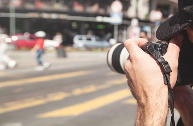 Der fotograf fotografiert mit einer dslr-kamera in einer stadt.