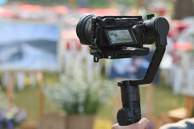 Der fotograf videokameramann an stabilisatoren arbeitet mit seiner ausrüstung, um genau darauf zu achten, ein foto zu machen.
