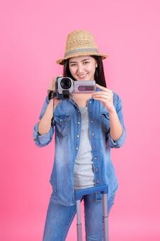 Der frauenreisende, der zughut trägt, hält videorecorder, porträt des hübschen lächelnden glücklichen jugendlichen auf rosa