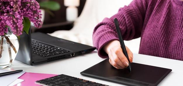 Der freiberufliche grafiker arbeitet von zu hause aus. frau zeichnet auf grafiktablett im heimbüro unter verwendung des laptops und des computers. fernarbeit im gemütlichen heimbüro mit blumen.