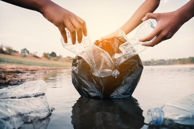 Der freiwillige, der einen flaschenplastik im fluss aufhebt, schützt umwelt vor einem verschmutzungskonzept.