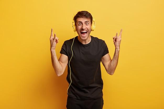 Der freudige junge hipster hört rockmusik in stereokopfhörern