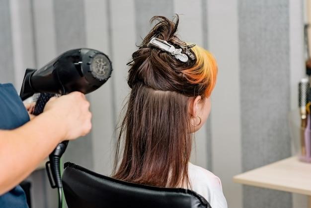 Der friseur färbt die haare des mädchens im schönheitssalon. mode gefärbte gebleichte pony. haar