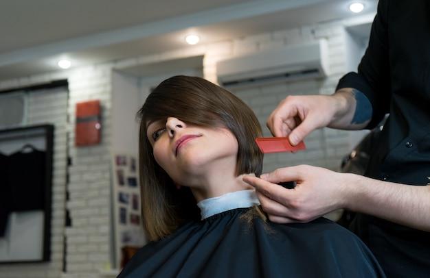 Der friseur kämmt das model vor dem haareschneiden im schönheitssalon.