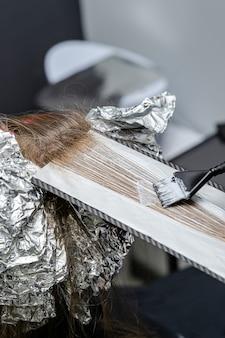 Der friseur macht dünne strähnen dick und trägt bleichpulver in shatush-technik auf.