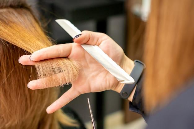 Der friseur schneidet der jungen frau im schönheitssalon braune haare