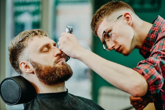 Der friseur schneidet einem mann im salon den bart