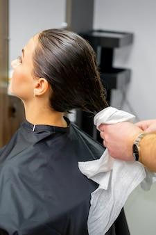 Der friseur trocknet das gewaschene haar mit einem handtuch an eine schöne junge brünette in einem schönheitssalon