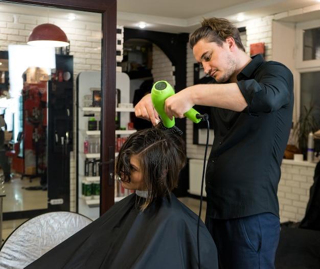 Der friseur trocknet die haare der schönen frau mit einem haartrockner