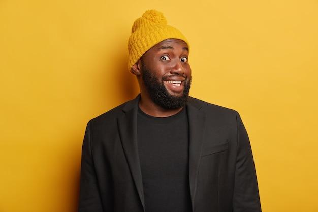 Der fröhliche afroamerikaner sieht mit neugierigem glücklichem ausdruck aus