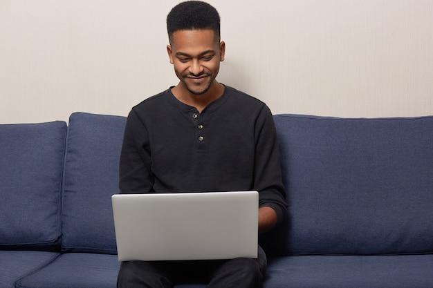 Der fröhliche afroamerikaner sitzt freiberuflich auf der couch vor einem geöffneten laptop, erledigt entfernte arbeit, trägt ein lässiges outfit und genießt die häusliche atmosphäre