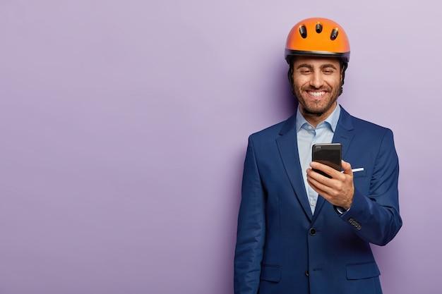 Der fröhliche architekt trägt einen orangefarbenen helm, einen formellen anzug, hat während der arbeitspause freizeit, erhält eine nachricht auf dem smartphone und freut sich über das gehalt