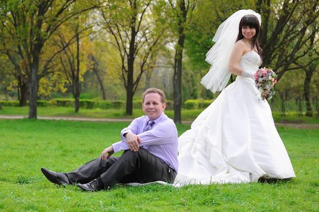 Der fröhliche bräutigam sitzt auf dem kleid der braut