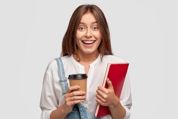 Der fröhliche doktorand trägt ein weißes hemd, hält kaffee und notizbuch heraus, lächelt positiv, isoliert über der weißen wand. weibliche auszubildende modelle drinnen, zufrieden mit etwas