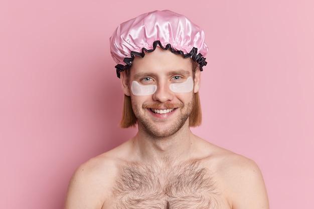 Der fröhliche europäische mann lächelt und trägt gerne kollagenkissen unter den augen auf. er wird einer schönheitsbehandlung unterzogen, bevor er ohne hemd zum duschen geht