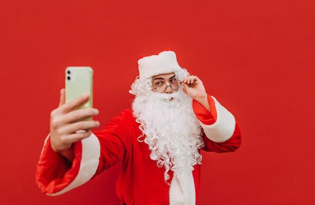 Der fröhliche fotogene weihnachtsmann posiert für ein handy-selfie