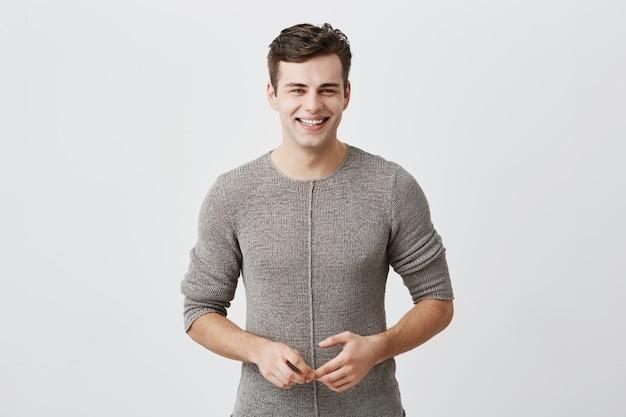Der fröhliche, gutaussehende kaukasische mann lächelt glücklich, hat einen aufgeregten ausdruck, ist lässig gekleidet, feiert sein jubiläum oder seine beförderung bei der arbeit. menschen, jugend, emotionen konzept