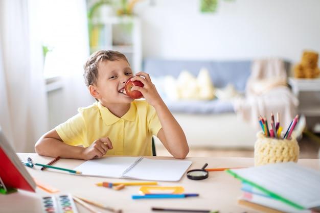 Der fröhliche junge beißt apple ab, der am schreibtisch sitzt, nachdem er die hausaufgaben in der schule erledigt hat