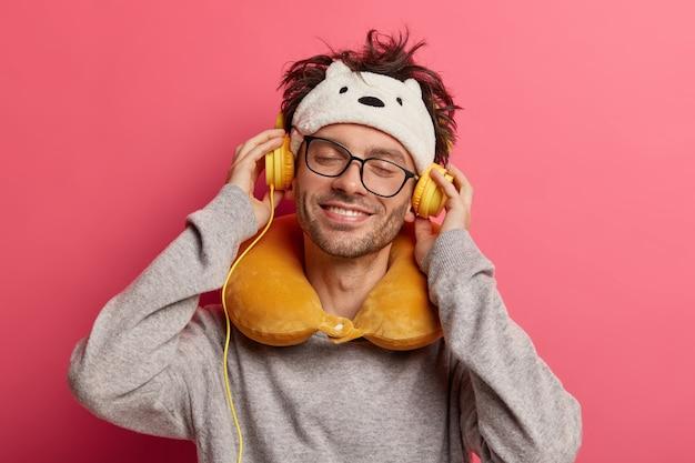 Der fröhliche junge mann hört musik über kopfhörer und lächelt angenehm