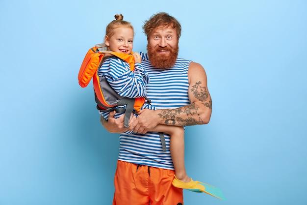 Der fröhliche junge mann posiert mit dem kleinen ingwermädchen, das orangefarbene schwimmweste, gummiflossen trägt, glücklich, sommerferien mit vater zu verbringen, genießt das schwimmen