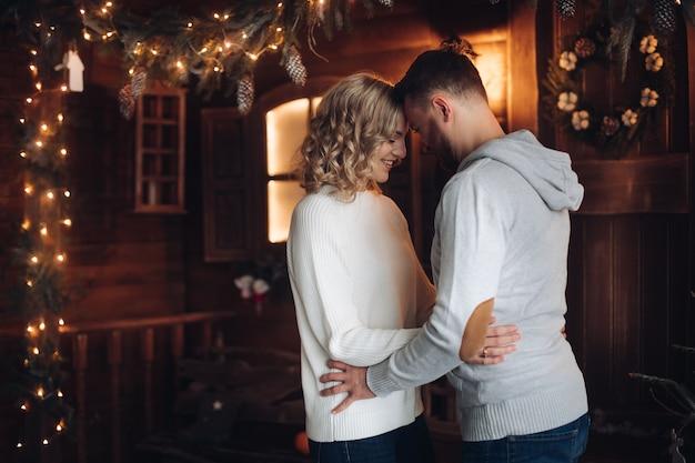 Der fröhliche kaukasische mann mit seiner attraktiven freundin in den gleichen kleidern verbringt vor weihnachten viel zeit miteinander zu hause