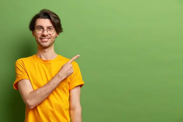 Der fröhliche kaukasische mann zeigt mit dem zeigefinger auf den kopierraum und schlägt ein sonderangebot vor
