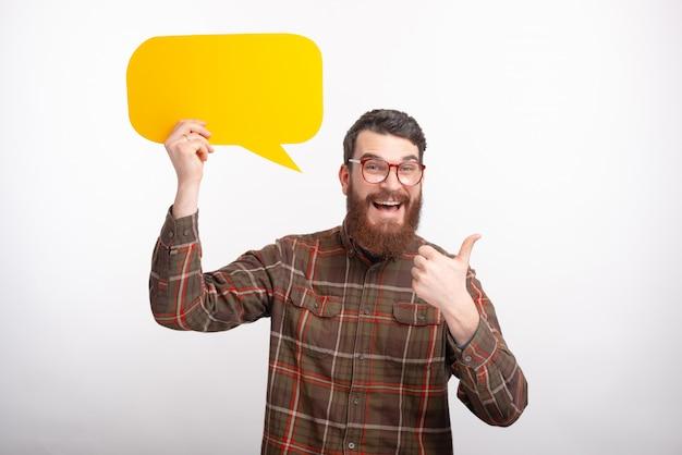 Der fröhliche männliche student zeigt daumen hoch und hält eine gelbe blasenrede auf weißem hintergrund.