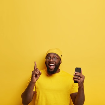 Der fröhliche mann zeigt mit dem zeigefinger nach oben, erstellt einen eigenen blog, surft auf smartpphone in sozialen medien und hat den gesichtsausdruck begeistert