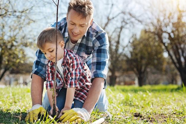 Der fröhliche vater bringt seinem kleinen sohn bei, sich um die natur zu kümmern, indem er einen baum in einen familiengarten pflanzt