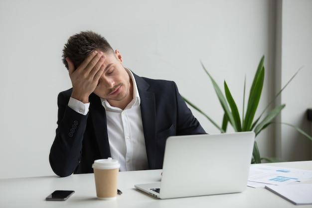 Der frustrierte tausendjährige geschäftsmann, der starke kopfschmerzen hat, ermüdete von der laptoparbeit