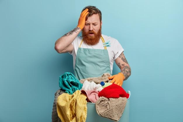 Der frustrierte, überwältigte, verwirrte, fuchsige mann hat viel arbeit mit dem haus, hält die hand auf dem kopf und starrt auf einen korb voller wäsche, hat zu hause waschzeit, weiß nicht, wie er anfangen soll, gekleidet in eine schürze