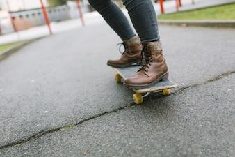 Der Fuß der Frau, der auf Skateboard im Park steht