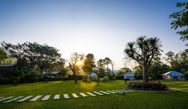 Der fußweg auf grünen rasenflächen und zelt mit sonnenaufgang im garten