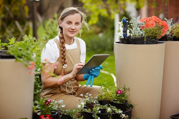 Der gärtner prüft den zustand und die verfügbarkeit von blumen, prüft anhand der einträge auf dem tablett.