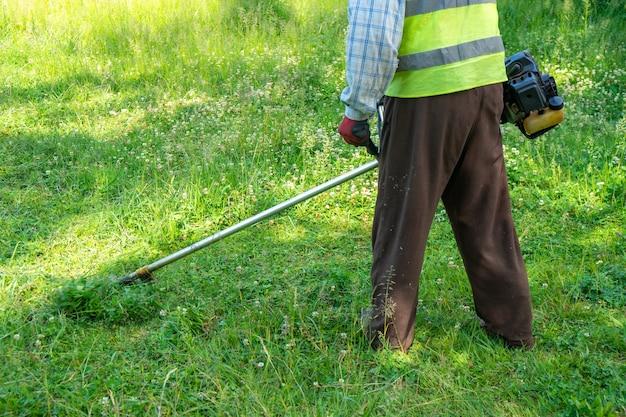 Der gärtner schneidet gras mit rasenmäher, rasenpflege. natur