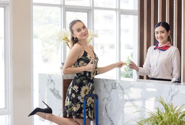 Der gast bezahlt die karte für dienstleistungen am check-in-schalter des hotels, kunden checken in ein resort ein