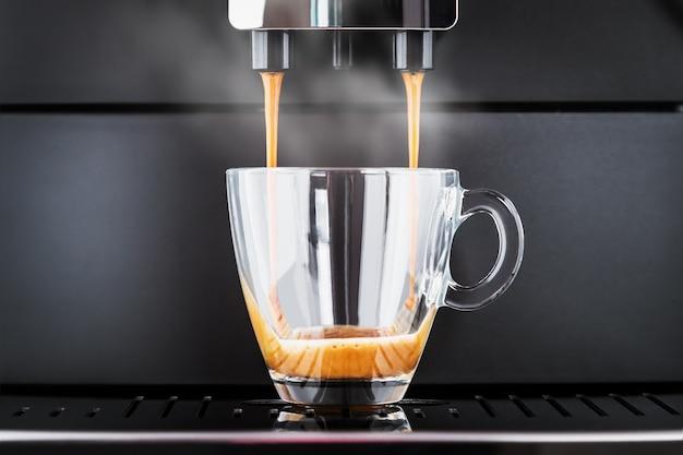 Der gebrühte kaffee wird aus der kaffeemaschine in eine glastasse gegossen