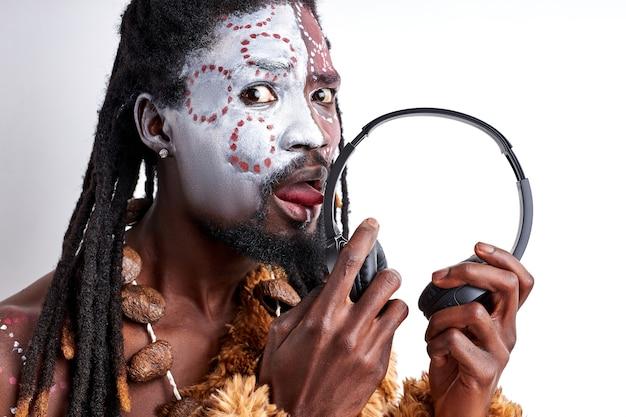 Der gebürtige afrikaner schmeckt kopfhörer, leckt sie, benutzt sie falsch. männlich in ethnischen aborigen tragen isoliert über weißer wand