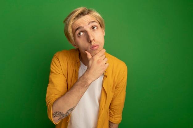 Der gedanke, den jungen blonden mann mit gelbem t-shirt nach oben zu schauen, packte das kinn