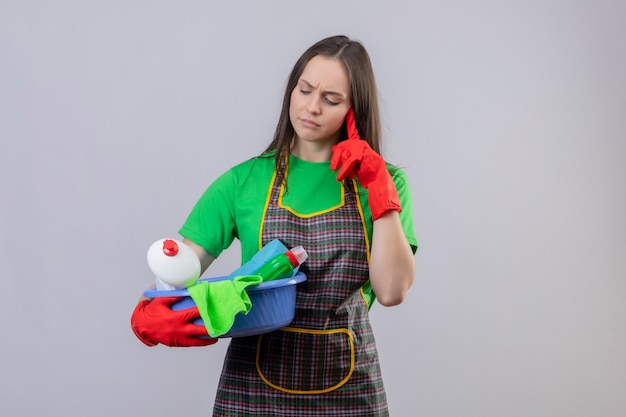 Der gedanke, junges mädchen in uniform in roten handschuhen zu reinigen, das reinigungswerkzeuge auf ihrer hand sucht, legte ihren finger auf wange auf isolierte weiße wand