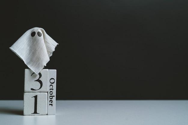 Der geist mit dem oktoberkalender und fledermäusen mit kopienraum halloween-feiertag